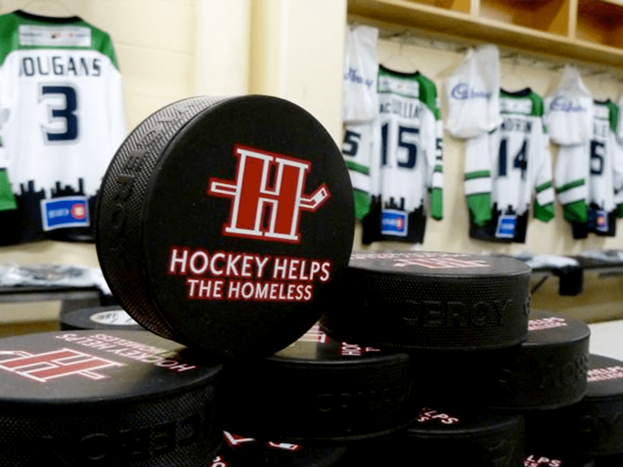 hockey puck with hockey helps the homeless logo on it
